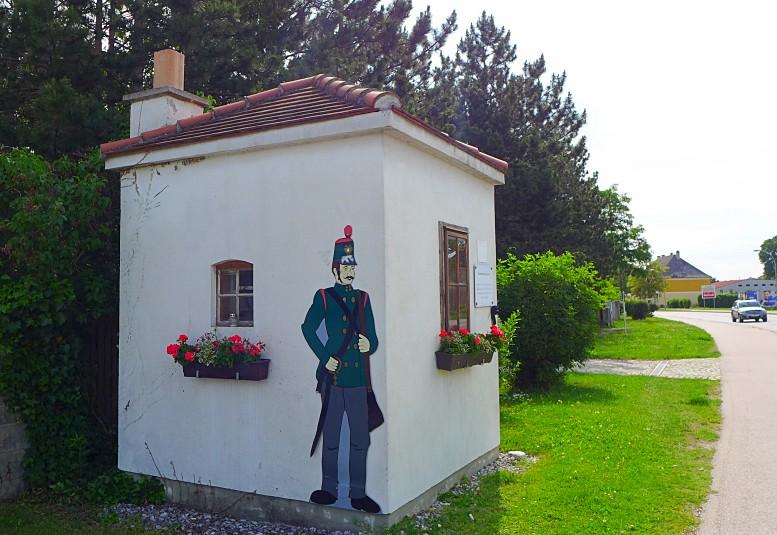 """Auf der am Neudörfler Grenzwächterhäuschen angebrachten Infotafel ist zu lesen: """"Die Leitha war von 1031–1921 Grenzfluss zwischen Österreich und Ungarn. Hier war einer der wenigen Grenzübergänge. Dieses Häuschen diente den Zöllnern als Unterstand."""" (Foto: B. Denscher)"""