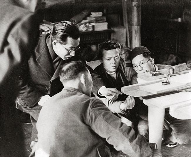 Charlotte Perriand studiert mit Möbeltischlern die Herstellung eines Tisches aus Kiefernbrettern, 1940, (c) Archiv Charlotte Perriand / Elisabeth Sandmann